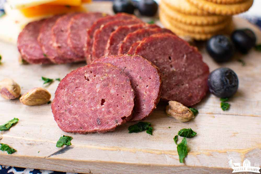 slices of homemade beef summer sausage on a wooden board with blueberries, pistachios, and crackers