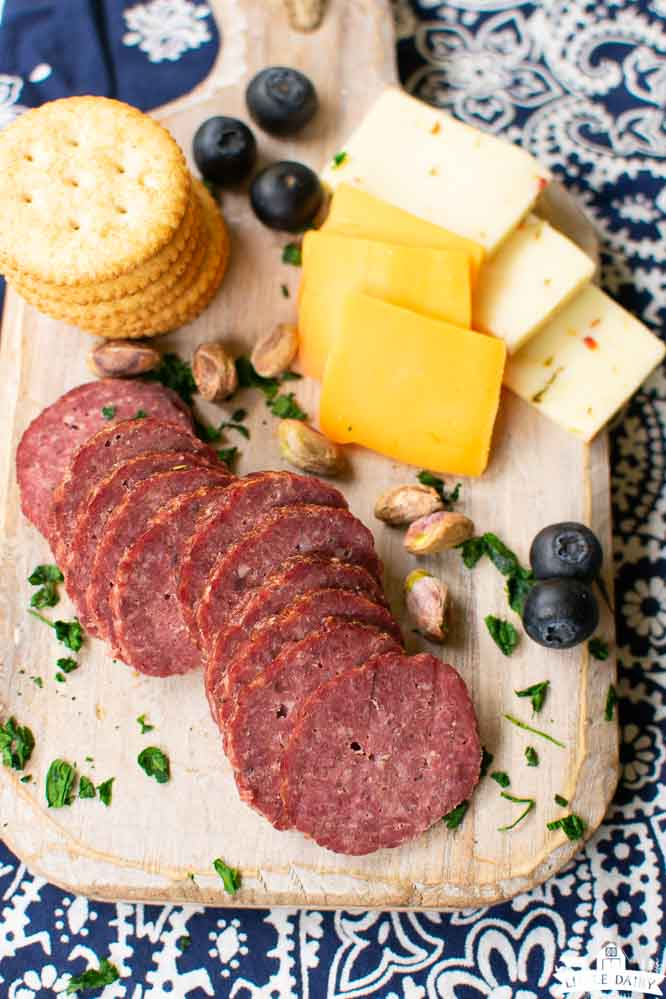 a wooden board with slices of baked summer sausage, sliced cheese, and crackers
