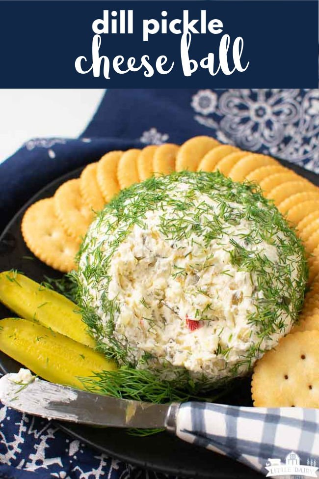 a cheese ball that's has a portion of it removed to show the inside of the cheese ball. On a black plate with round crackers and pickle slices
