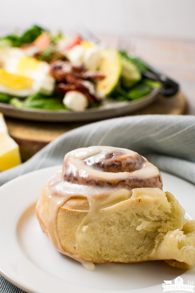 a cinnamon roll with icing and a breakfast salad in the background