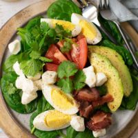 A healthy, savory breakfast salad with layers of spinach, eggs, tomatoes, cheese, avocado, and bacon.