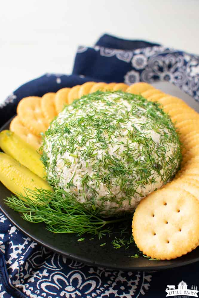 a cheeseball sprinkled with minced fresh dill weed, surrounded by butter crackers and pickle slices