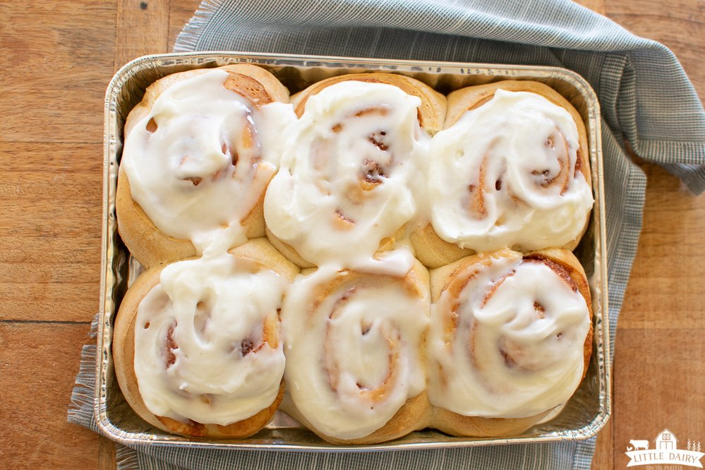 a tin pan with baked and frosted 30-minute cinnamon rolls