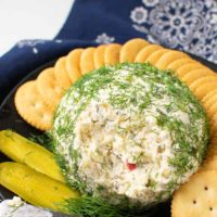 a cheese ball made with dill pickle relish and covered with fresh dill weed, surrounded by butter crackers and a pickle slice.