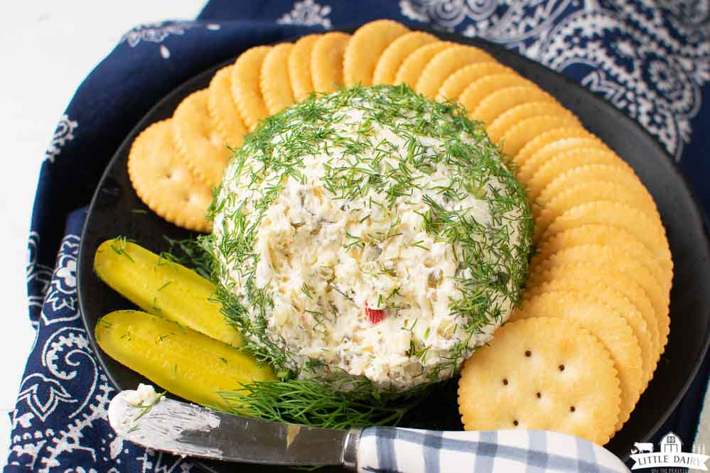 A black plate with a cheese ball covered with fresh dill weed and a knife for spreading cream cheese dip. Surrounded by Ritz crackers. Little Dairy on the Prairie