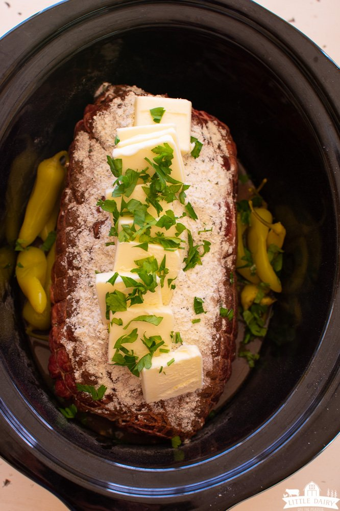 a slow cooker with an uncooked roast sprinkled with dry ranch seasoning, au jus, and topped with slices of butter and chopped parsley. Pepperoncini's on the sides.