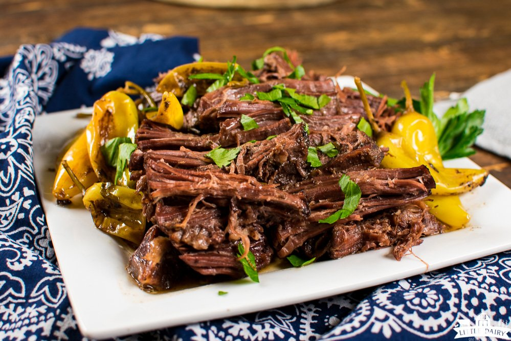 a square white plate with a shredded roast beef, chopped parsley, and pepperoncini or banana peppers on the side. Little Dairy on the Prairie