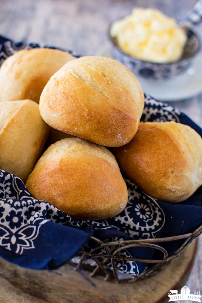 a wire basket filled with baked dinner rolls