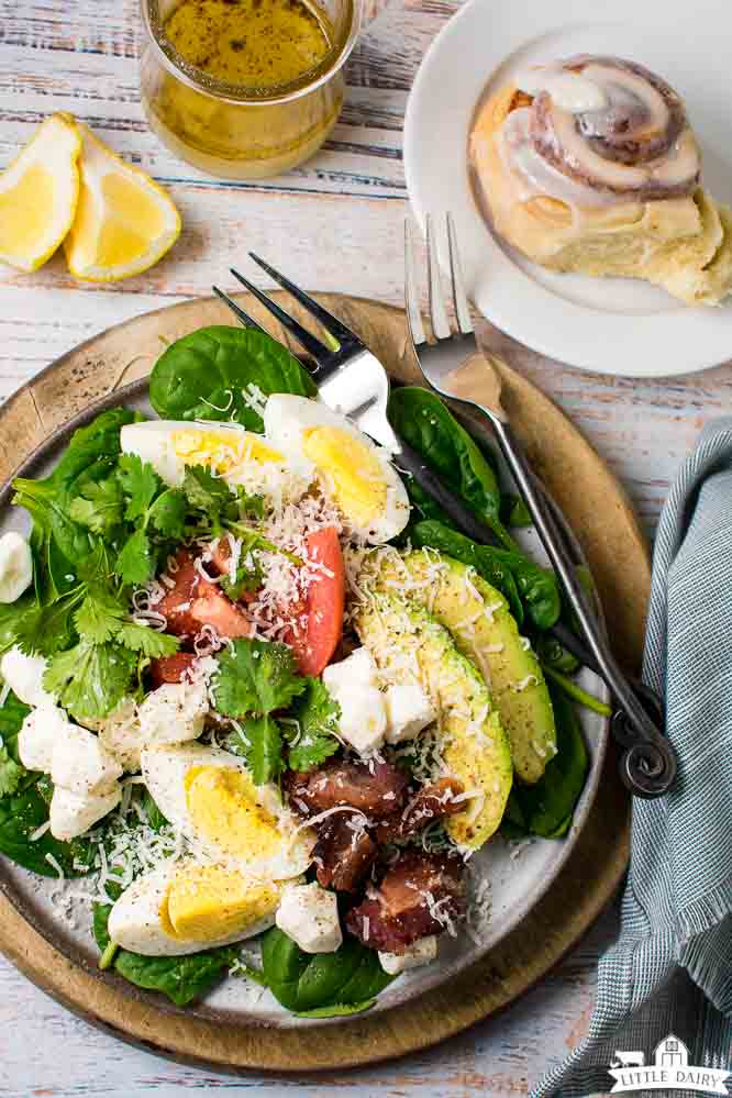 a green salad on a plate with a wooden charger, forks, lemon wedges, salad dressing and a cinnamon roll