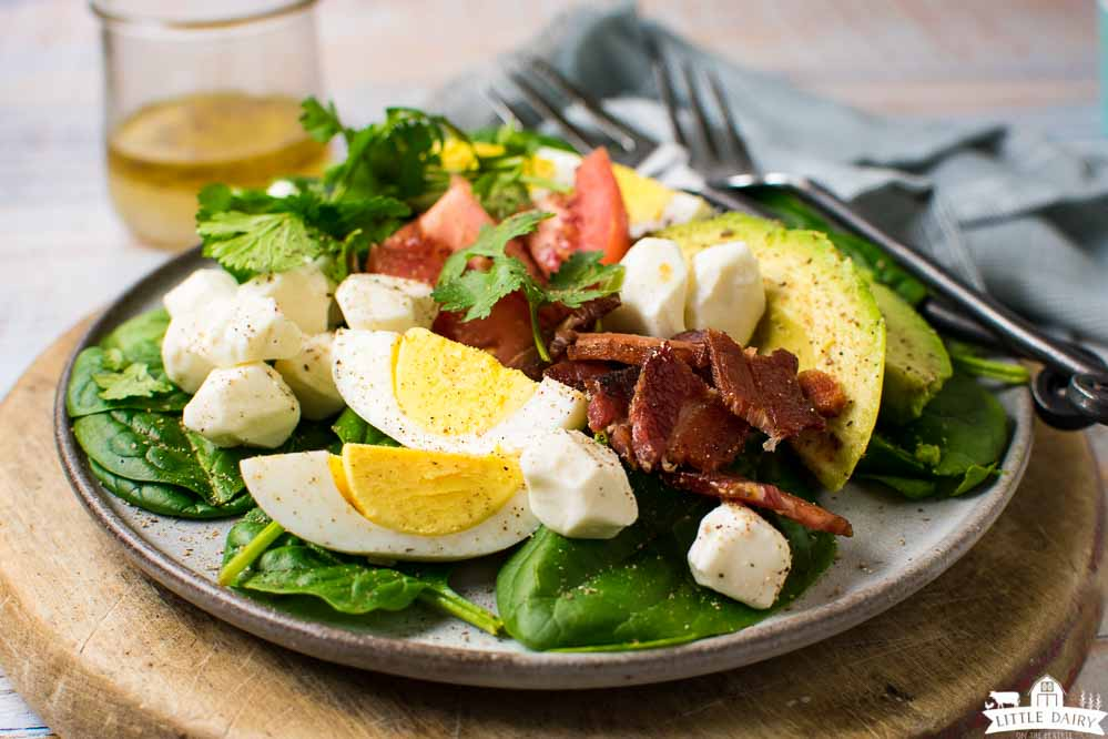 a plate with a savory breakfast salad loaded with eggs, bacon, and other breakfast vegetables