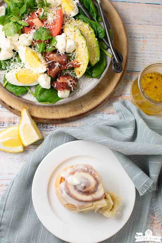 a baked and frosted cinnamon roll and a plate with a savory breakfast salad loaded with vegetables