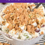 a white bowl of grape salad in a creamy dressing, topped with brown sugar and walnuts plus a text overlay