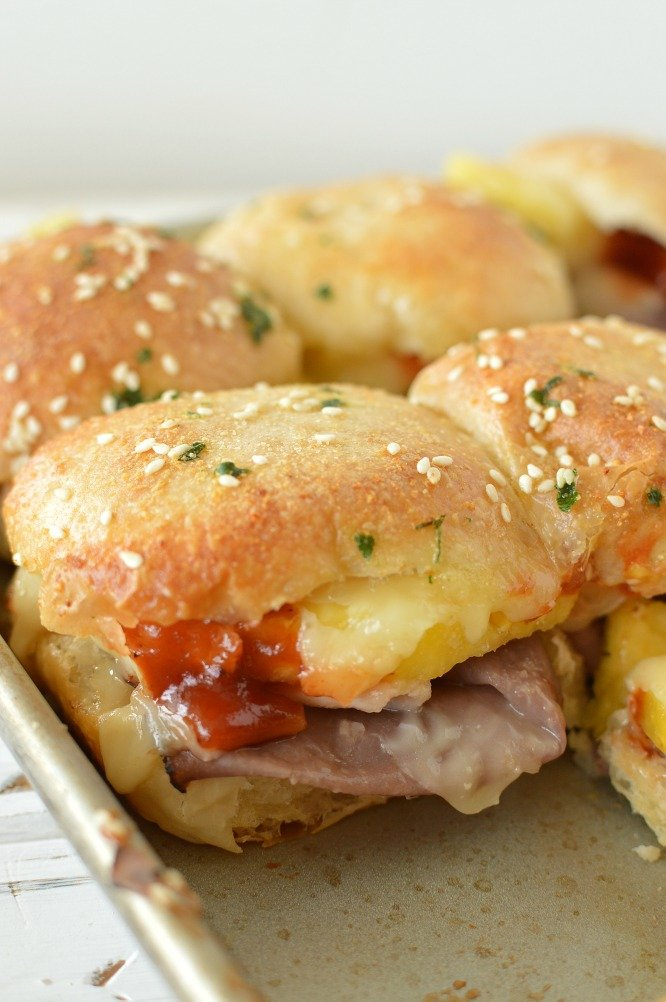 a baking sheet with roast beef and cheese sandwiches that have been baked until golden brown
