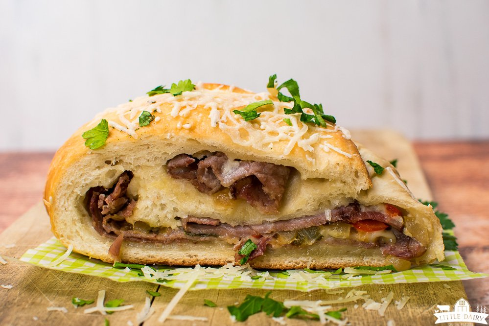 a slice of baked steak and cheese stromboli on a white and green parchment paper topped with fresh parsley and cheese