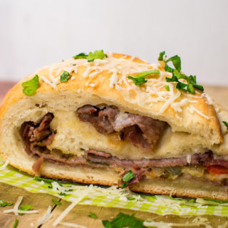 a slice of cheesesteak stromboli rolled up with layers of cheese, steak, and peppers and onions