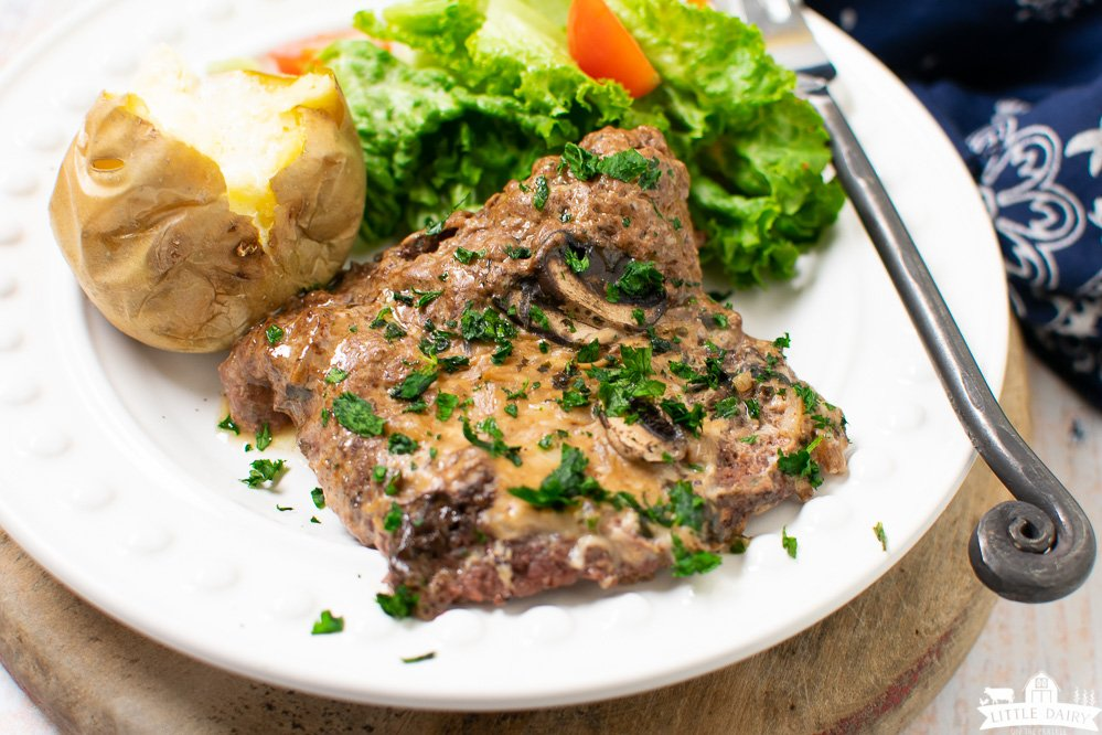 A white plate with cooked cube steak in gravy and green salad and a potato