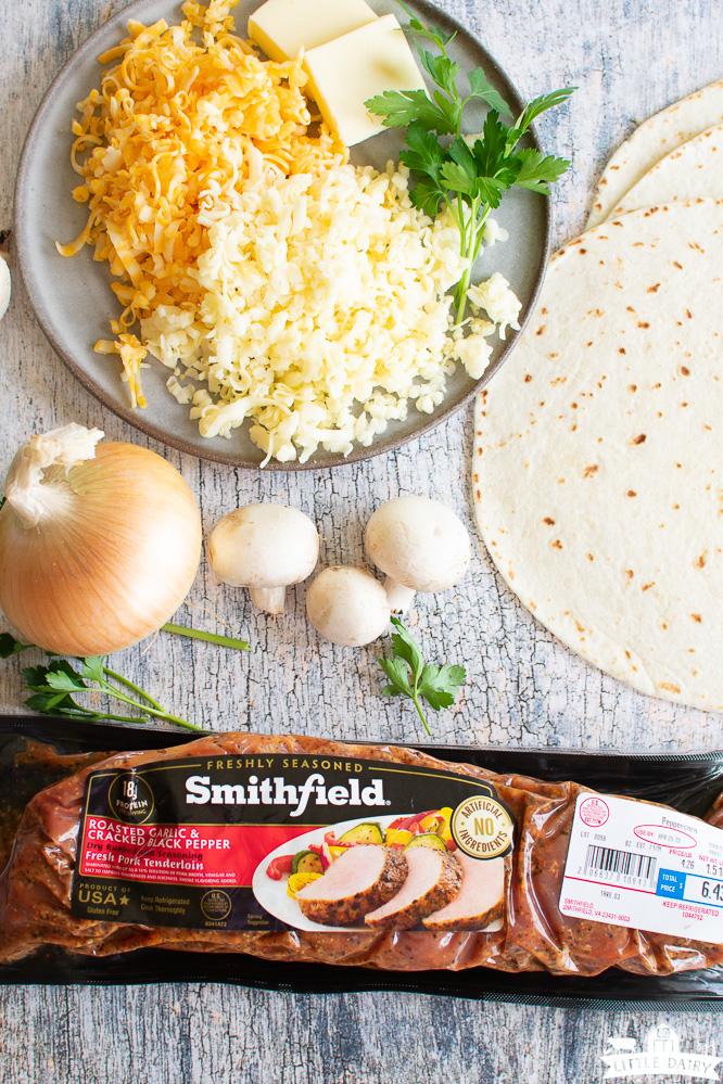 piles of cheese, flour tortillas, mushrooms, an onion, and a pork tenderloin