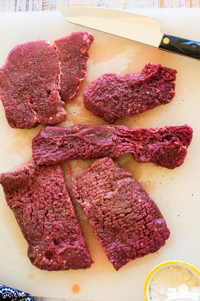 raw cube steaks on a cutting board