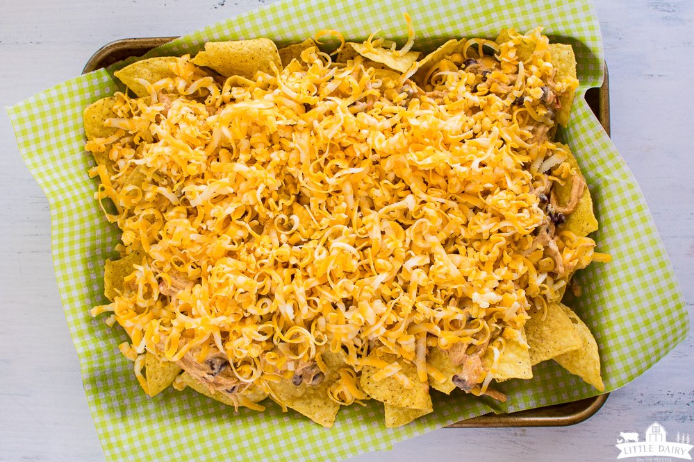 sheet pan with tortilla chips covered with shredded cheese