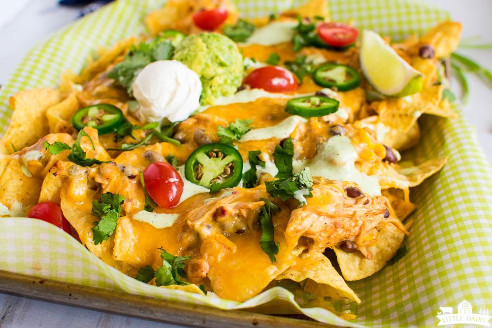 creamy chicken nachos topped with jalapenos, cilantro, sour cream, guacamole