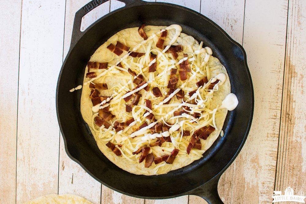 cast iron skillet with tortilla topped with shredded cheese, diced bacon, and ranch dressing