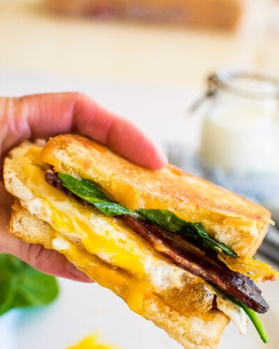 a hand holding half a fried egg sandwich on white toast, and has spinach and bacon