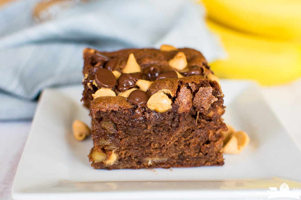 a square of brownie topped with chocolate chips and peanut butter chips on a white plate with bananas in the background