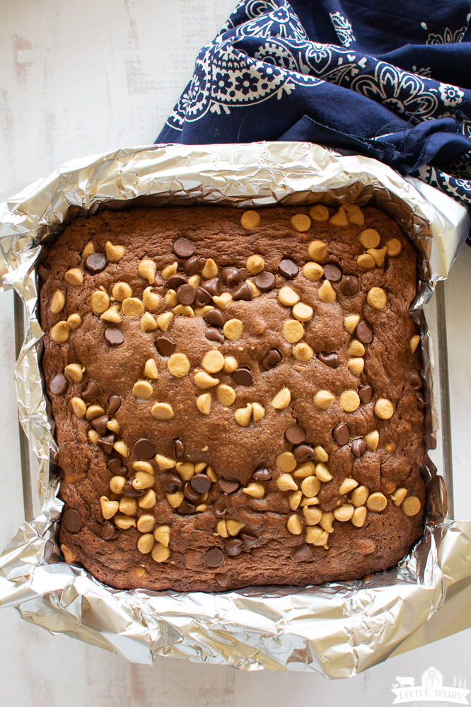 a glass pan lined with aluminum foil with baked brownies topped with chocolate chips and peanut butter chips