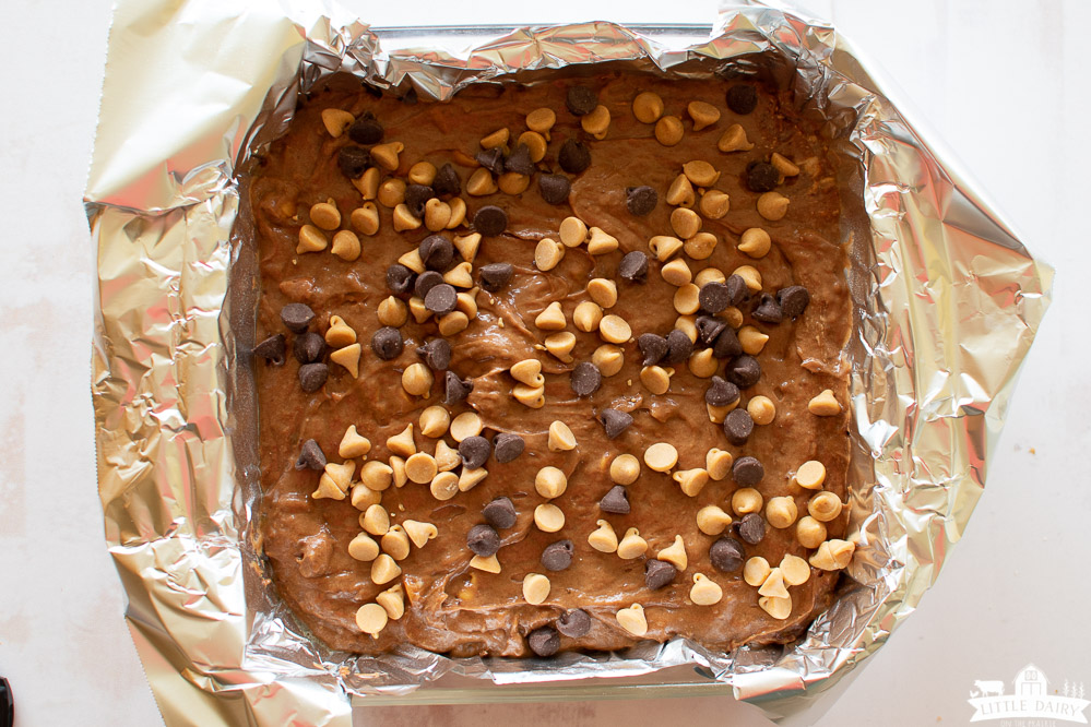 a 9 x9 inch glass baking pan lined with aluminum foil filled with brownie batter topped with chocolate chips and peanut butter chips