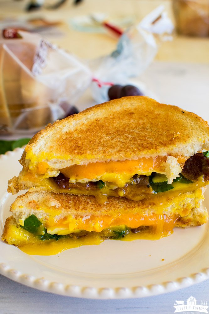 Two halves of breakfast grilled cheese stacked on top of each other. Sandwiches are filled with melted cheese, spinach, a fried egg that's dripping, and bacon.