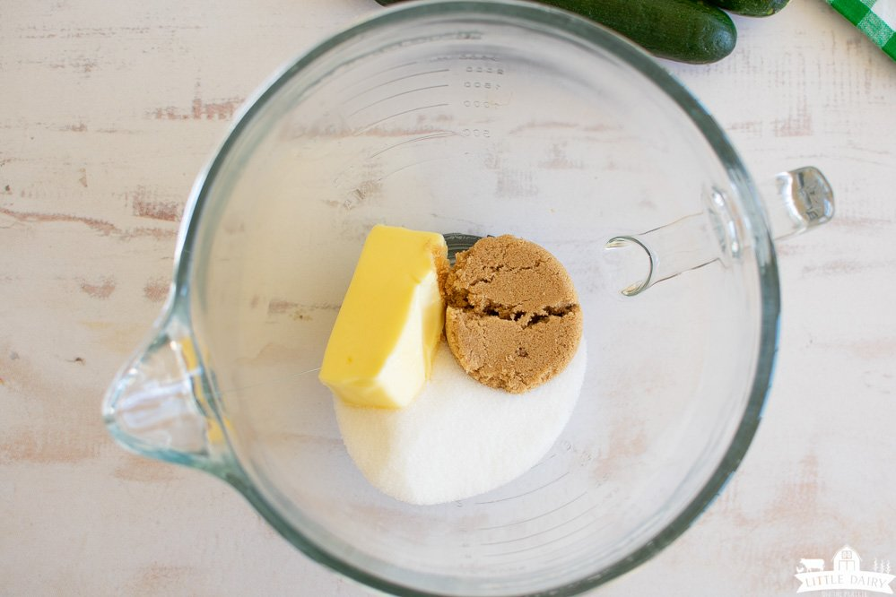 a cube of butter, brown sugar, and white sugar in a glass mixing bowl