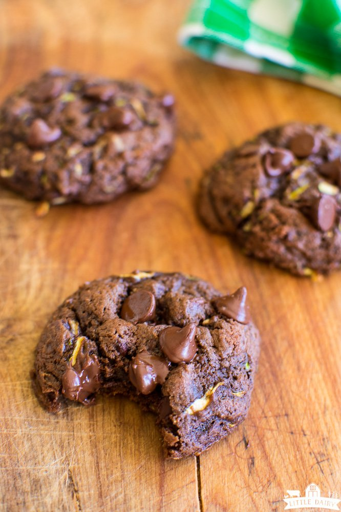a wooden board with three chocolate chocolate chip zucchini cookies