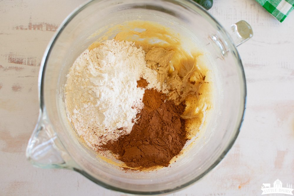 a glass mixing bowl with creamed butter and sugar, topped with flour and cocoa