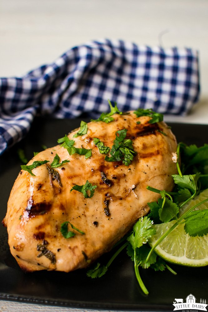 grilled chicken breast with char marks, sprinkled with herbs and garnished with limes. On a black plate with blue and white gingham napkin.