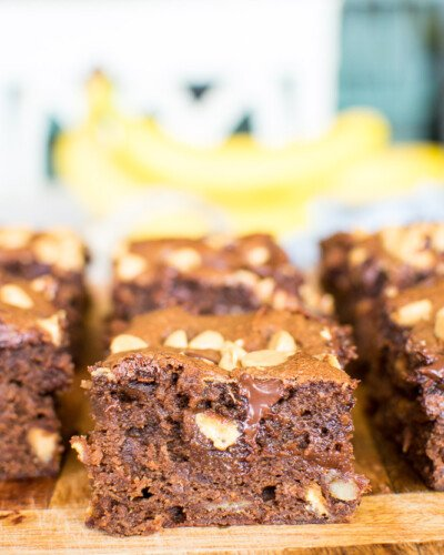 fudgy brownies with melted chocolate chips and chopped walnuts inside on a wooden cutting board