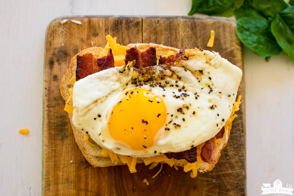 a sliced of bread topped with grated cheese, sliced of fried bacon, and a fried sunny side up egg.