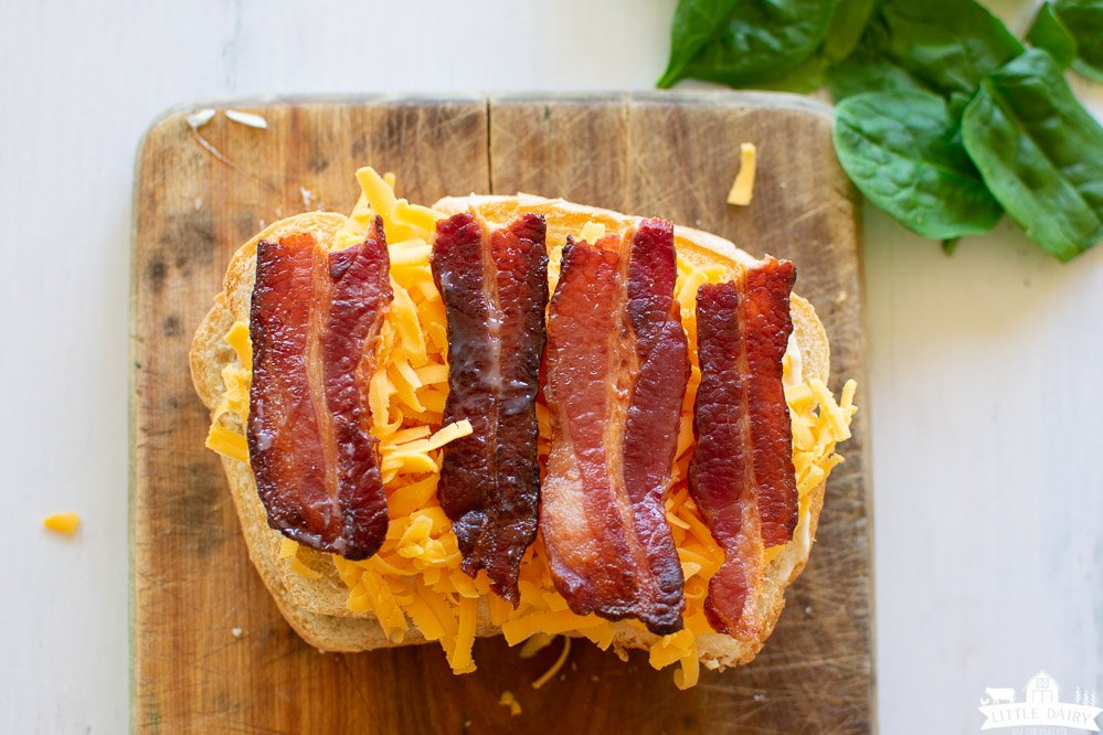 a slice of bread on a wooden cutting board topped with grated cheese and slices of cooked bacon