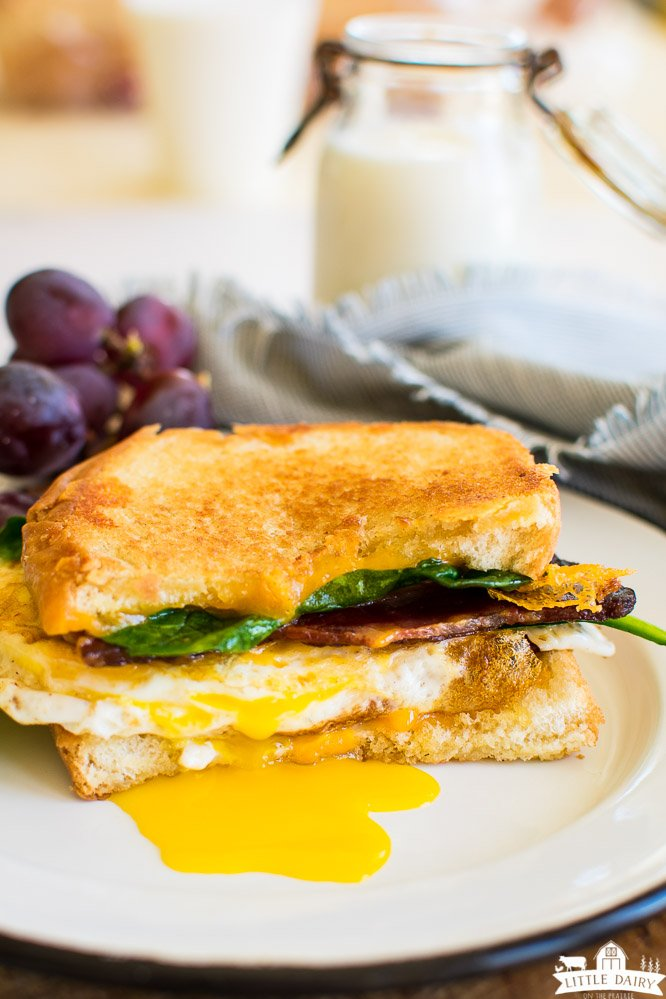 a grilled cheese sandwich with a fried egg, spinach, and bacon. Purple grapes and a jar of milk in the background