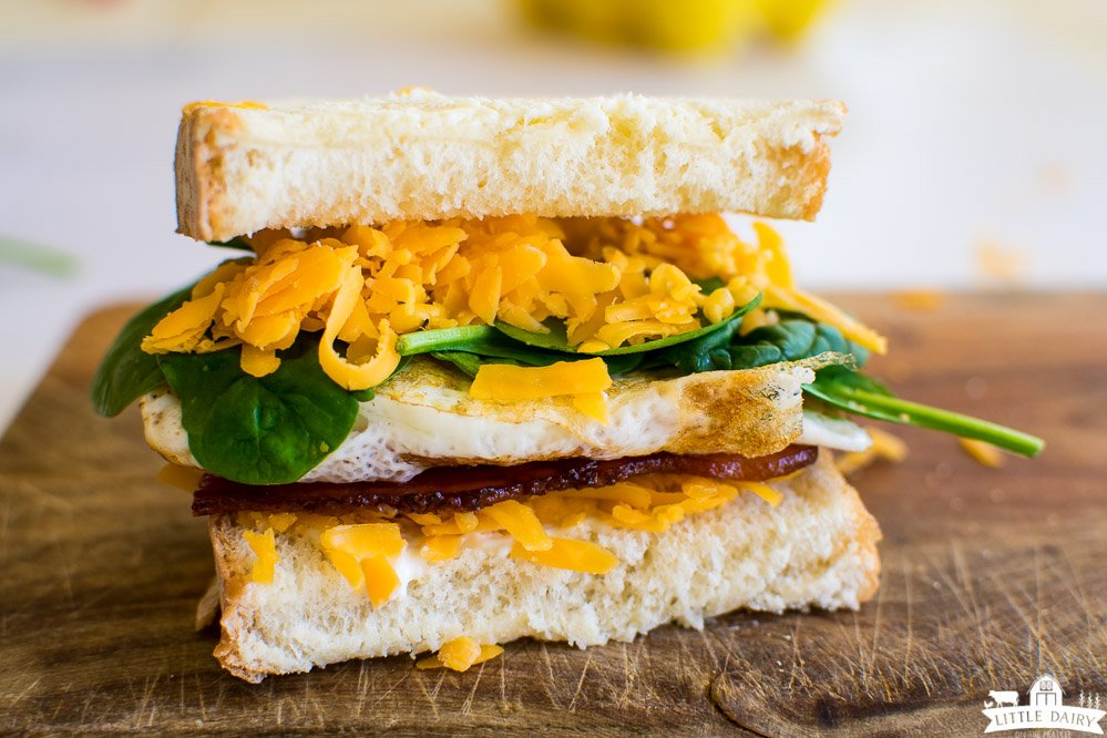 a front view of a sandwich with layers of grated cheese, a fried egg, spinach, and bacon on a wooden cutting board