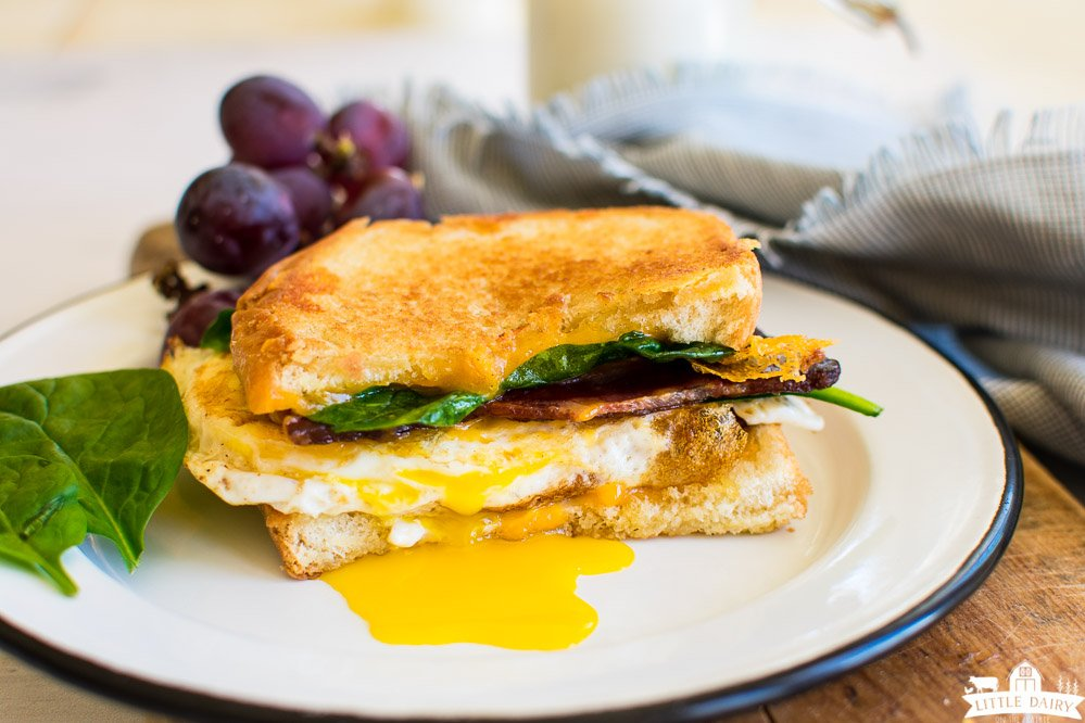 Half a breakfast grilled cheese sandwich with bacon, fried egg, and spinach on a white plate, Red grapes and a blue napkin in the background.