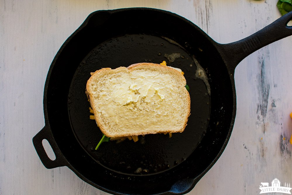 a cast iron skillet with a buttered grilled cheese sandwich not grilled yet.