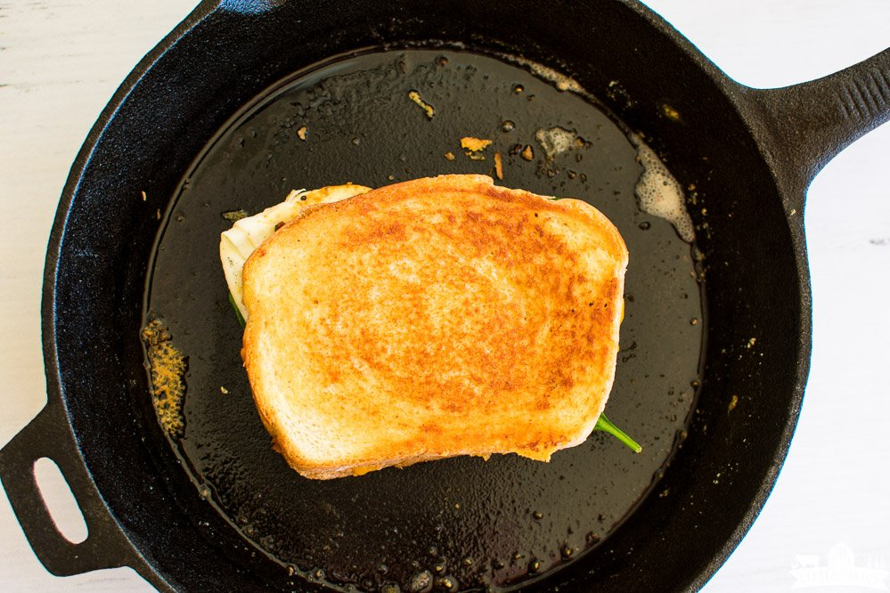 a golden brown grilled cheese sandwich in a cast iron skillet