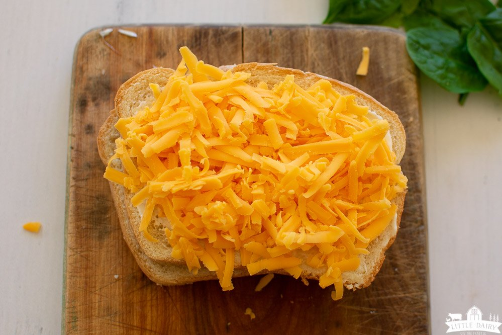 two pieces of white bread stacked on top of each other and topped with grated cheese sitting on a wooden cutting board.
