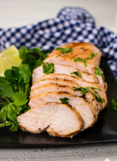 Sliced grilled chicken showing how juicy it is, garnished with cilantro on a black plate