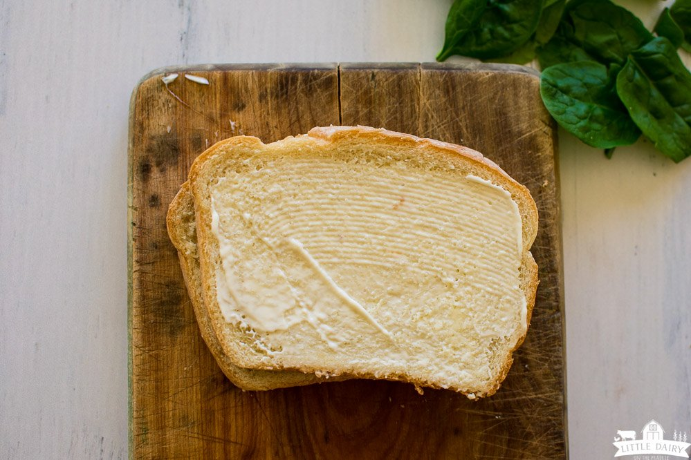 two slices of buttered bread stacked on top of each other on a wooden cutting board, baby spinach leaves in the top right corner