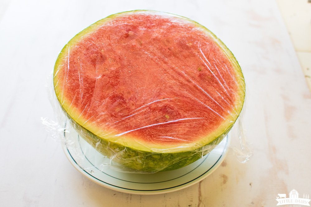 half a watermelon still in the rind, covered with plastic wrap.