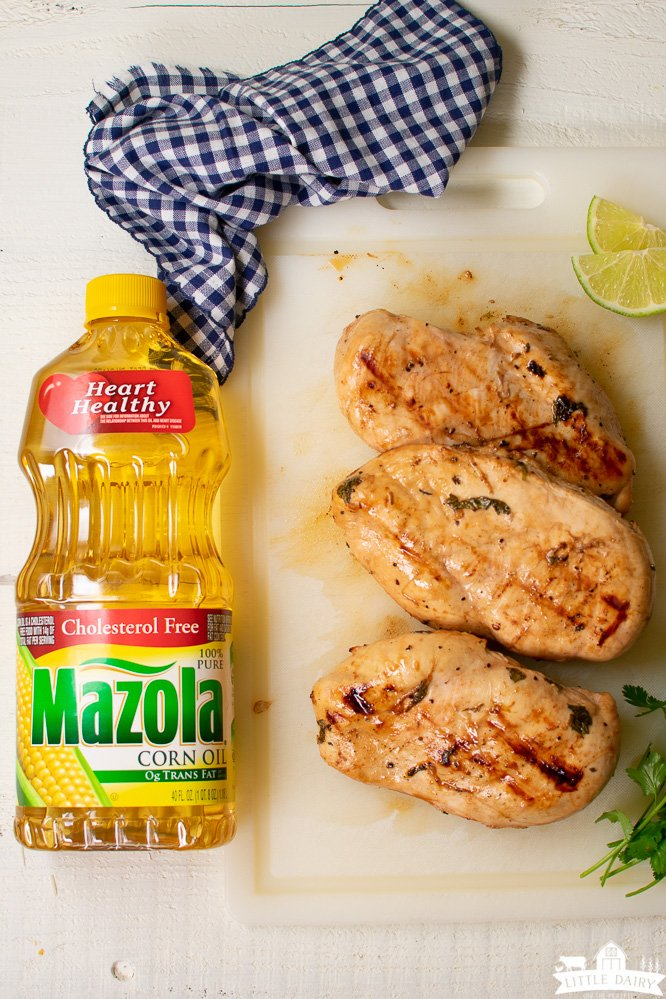 grilled chicken with a bottle of corn oil and a blue checkered napkin