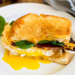 Half a fried egg grilled cheese sandwich with spinach and bacon. Red grapes in the background.