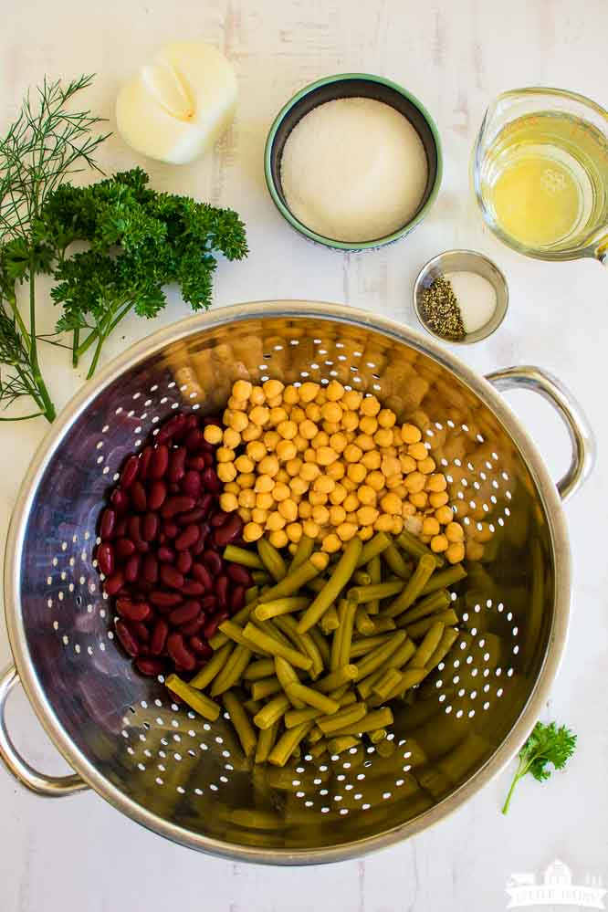 a colander with green beans, chick peas, and kidney beans, plus a dish with sugar, salt and pepper, and fresh herbs