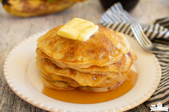 a stack of pancakes on a white plate with butter and syrup with bananas in the back